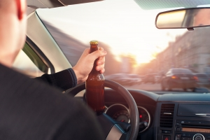 Man drinking alcohol while driving a car. Transportation and vehicle safety.