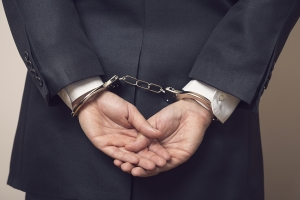 Business man in a suit with handcuffs under arrest for corruption and bribery. Selective focus