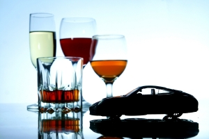 Photo of an alcoholic drink in a crystal glass and a toy car
