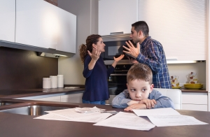 Sad child suffering and his parents having hard discussion in a home kitchen by couple difficulties