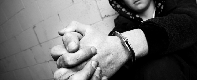 teen in handcuffs against wall with dirty hands and handcuffs converted to black and white with slight added grain. focus on cuffs.