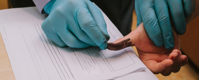 Los Angeles Criminal Lawyer - The investigation of the crime. The inspector takes fingerprints of a suspect.