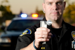 A police officer holding a breath test machine with his police car in the background
