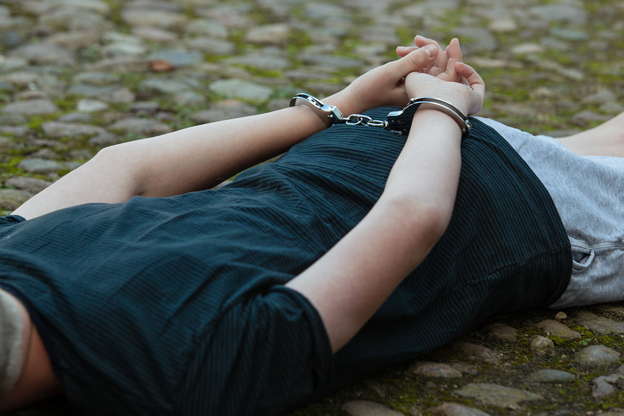 Los Angeles Criminal Defense Lawyer - Young boy being arrested by the police lying on cobblestones outdoors with his hands cuffed behind his back in handcuffs close up torso view
