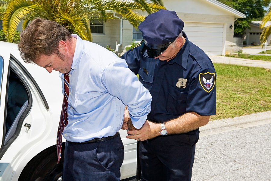 White collar crime Businessman being handcuffed and placed under arrest in front of his home.